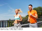 Купить «couple with fitness trackers running along bridge», фото № 30527603, снято 5 июля 2015 г. (c) Syda Productions / Фотобанк Лори