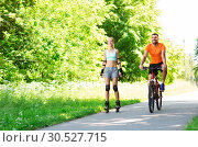 Купить «happy couple with rollerblades and bicycle riding», фото № 30527715, снято 5 июля 2015 г. (c) Syda Productions / Фотобанк Лори