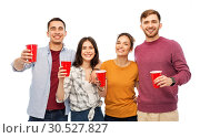 Купить «group of smiling friends with drinks in party cups», фото № 30527827, снято 10 ноября 2018 г. (c) Syda Productions / Фотобанк Лори