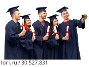 Купить «graduates with diplomas taking selfie by cellphone», фото № 30527831, снято 10 ноября 2018 г. (c) Syda Productions / Фотобанк Лори