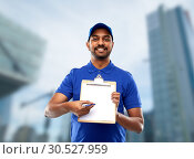 Купить «happy indian delivery man with clipboard in blue», фото № 30527959, снято 12 января 2019 г. (c) Syda Productions / Фотобанк Лори