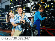 Купить «Cheerful couple sitting on motorcycle at service point», фото № 30528347, снято 19 апреля 2019 г. (c) Яков Филимонов / Фотобанк Лори