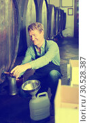 Smiling man working in winery pouring wine from wood to plastic bottle in cellar. Стоковое фото, фотограф Яков Филимонов / Фотобанк Лори