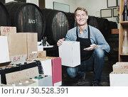 Купить «Man seller wearing apron having package box with wine bottles», фото № 30528391, снято 25 мая 2019 г. (c) Яков Филимонов / Фотобанк Лори