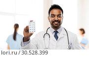 Купить «indian male doctor with pills and stethoscope», фото № 30528399, снято 12 января 2019 г. (c) Syda Productions / Фотобанк Лори