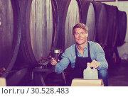 Купить «Male seller in wine cellar», фото № 30528483, снято 21 сентября 2019 г. (c) Яков Филимонов / Фотобанк Лори