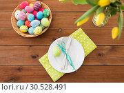 Купить «easter eggs in basket, plates, cutlery and flowers», фото № 30528491, снято 15 марта 2018 г. (c) Syda Productions / Фотобанк Лори