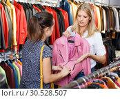 Polite smiling seller communicating with female customer in leather clothes shop. Стоковое фото, фотограф Яков Филимонов / Фотобанк Лори
