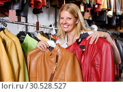 Купить «Portrait of satisfied female customer with leather jackets in store», фото № 30528527, снято 5 сентября 2018 г. (c) Яков Филимонов / Фотобанк Лори