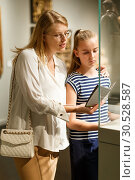 Girl with woman looking with interest at art objects in museum. Стоковое фото, фотограф Яков Филимонов / Фотобанк Лори