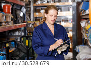 Купить «Woman holding notebook and looking tools at shelves during inventory in build store», фото № 30528679, снято 20 сентября 2018 г. (c) Яков Филимонов / Фотобанк Лори