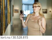 Купить «Woman looking at exposition and taking pictures», фото № 30528815, снято 22 сентября 2018 г. (c) Яков Филимонов / Фотобанк Лори
