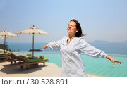 Купить «happy woman enjoying sun over infinity edge pool», фото № 30528891, снято 15 июня 2018 г. (c) Syda Productions / Фотобанк Лори