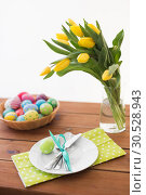 Купить «easter eggs in basket, plates, cutlery and flowers», фото № 30528943, снято 15 марта 2018 г. (c) Syda Productions / Фотобанк Лори