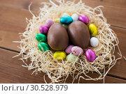 Купить «chocolate eggs and candies in straw nest», фото № 30528979, снято 22 марта 2018 г. (c) Syda Productions / Фотобанк Лори