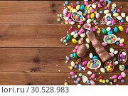 Купить «chocolate eggs, easter bunny and candies on wood», фото № 30528983, снято 22 марта 2018 г. (c) Syda Productions / Фотобанк Лори