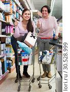 Купить «two women having shopping carts and choosing goods in cosmetics store», фото № 30528999, снято 18 апреля 2019 г. (c) Яков Филимонов / Фотобанк Лори