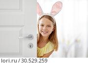 Купить «happy girl with easter bunny ears peeking out door», фото № 30529259, снято 25 июля 2018 г. (c) Syda Productions / Фотобанк Лори