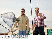 Купить «friends with fishing rod, fish and tackle on pier», фото № 30529279, снято 8 сентября 2018 г. (c) Syda Productions / Фотобанк Лори