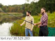 Купить «friends with fishing rods at lake or river», фото № 30529283, снято 8 сентября 2018 г. (c) Syda Productions / Фотобанк Лори
