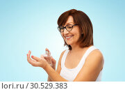 Купить «smiling senior woman spraying perfume to her wrist», фото № 30529383, снято 8 февраля 2019 г. (c) Syda Productions / Фотобанк Лори