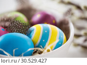 Купить «close up of colored eggs and feathers in bowl», фото № 30529427, снято 22 марта 2018 г. (c) Syda Productions / Фотобанк Лори