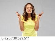 Купить «young woman or teenage girl with fingers crossed», фото № 30529511, снято 29 января 2019 г. (c) Syda Productions / Фотобанк Лори