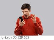 Купить «mad man in red hoodie screaming to smartphone», фото № 30529635, снято 3 февраля 2019 г. (c) Syda Productions / Фотобанк Лори