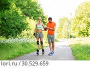 Купить «couple with roller skates riding in summer park», фото № 30529659, снято 5 июля 2015 г. (c) Syda Productions / Фотобанк Лори