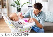 Купить «father feeding happy baby in highchair at home», фото № 30529699, снято 25 августа 2018 г. (c) Syda Productions / Фотобанк Лори