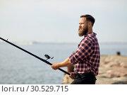 Купить «bearded fisherman with fishing rod on pier at sea», фото № 30529715, снято 8 сентября 2018 г. (c) Syda Productions / Фотобанк Лори