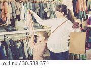 Купить «Choose a dress for a newborn girl», фото № 30538371, снято 10 января 2017 г. (c) Яков Филимонов / Фотобанк Лори