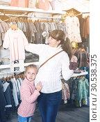 Купить «Mother and small daughter choosing clothes for baby», фото № 30538375, снято 10 января 2017 г. (c) Яков Филимонов / Фотобанк Лори