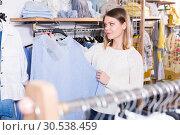 Купить «Smiling woman choosing blue sweater in the modern shop», фото № 30538459, снято 15 марта 2018 г. (c) Яков Филимонов / Фотобанк Лори