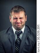 Businessman with screwed-up eyes. Стоковое фото, фотограф Tryapitsyn Sergiy / Фотобанк Лори