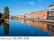 Купить «View of the Fontanka river with with English bridge in the distance, profitable houses on the waterfront and their mirror image in the water. Saint Petersburg, Russia», фото № 30541539, снято 26 мая 2018 г. (c) Наталья Волкова / Фотобанк Лори