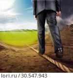 Купить «Businessman walking on tightrope», фото № 30547943, снято 30 апреля 2011 г. (c) Tryapitsyn Sergiy / Фотобанк Лори