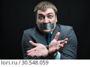 Купить «Man with mouth covered by masking tape», фото № 30548059, снято 21 апреля 2014 г. (c) Tryapitsyn Sergiy / Фотобанк Лори