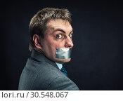 Купить «Man with mouth covered by masking tape», фото № 30548067, снято 21 апреля 2014 г. (c) Tryapitsyn Sergiy / Фотобанк Лори