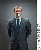 Купить «Man with mouth covered by masking tape», фото № 30548071, снято 21 апреля 2014 г. (c) Tryapitsyn Sergiy / Фотобанк Лори