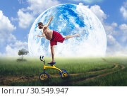 Nerdy man standing on a small bicycle. Стоковое фото, фотограф Tryapitsyn Sergiy / Фотобанк Лори