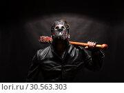 Купить «Bloody maniac in mask and black leather coat», фото № 30563303, снято 7 ноября 2016 г. (c) Tryapitsyn Sergiy / Фотобанк Лори