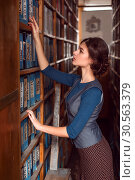 Купить «Woman taking a book from bookshelf.», фото № 30563379, снято 20 ноября 2016 г. (c) Tryapitsyn Sergiy / Фотобанк Лори