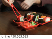 Купить «Keep sushi roll with chopsticks.», фото № 30563583, снято 25 ноября 2016 г. (c) Tryapitsyn Sergiy / Фотобанк Лори
