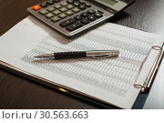 Accounting documents, pens and calculator closeup. Стоковое фото, фотограф Tryapitsyn Sergiy / Фотобанк Лори