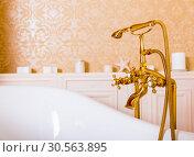 Rich gold faucet and white bath in the bathroom. Стоковое фото, фотограф Tryapitsyn Sergiy / Фотобанк Лори