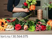 Купить «Florist with bouquet of roses at work.», фото № 30564075, снято 11 декабря 2016 г. (c) Tryapitsyn Sergiy / Фотобанк Лори