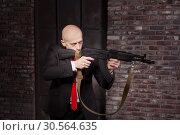 Купить «Killer in suit and red tie shoot a machine gun», фото № 30564635, снято 19 января 2017 г. (c) Tryapitsyn Sergiy / Фотобанк Лори