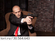 Купить «Bald killer in suit and red tie aims a pistol», фото № 30564643, снято 19 января 2017 г. (c) Tryapitsyn Sergiy / Фотобанк Лори