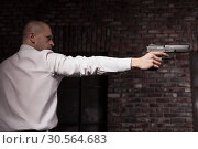 Serious hired murderer in red tie aims a gun. Стоковое фото, фотограф Tryapitsyn Sergiy / Фотобанк Лори
